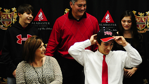 Thompson High School senior baseball player Stephan Poplin dons his Northwest Florida State College hat as, from left, his brother, Harrison, mother, Dawn, father, Stephan and sister, Madison, look on. (Reporter Photo/Neal Wagner)