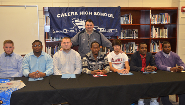 From left: Brandon Acker, Ty James, Adam Meadows, Frank Thomas, Austin Ford, Dez Kursh and Shakeith Tyes all pose for a picture in front of head fooball coach Wiley McKeller on March 20. All signed scholarships to play college football, except Acker, who signed a scholarship to be a member of the bassfishing team at Faulkner University. (Reporter Photo / Baker Ellis)