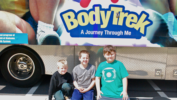 Soren WIlliams, Andrew Martin and Charles Pohlman wait for their turn to tour the BodyTrek mobile museum on March 25. (Reporter Photo / Molly Davidson)