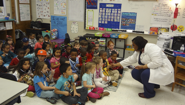 UAB emergency room physician Marquita Hicks shows students at Calera Elementary School how to use a stethoscope during Career Day on March 27. (Reporter Photo/Emily Sparacino)