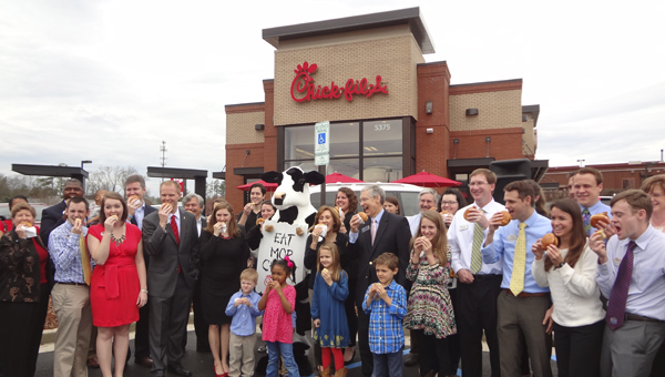 "Those gathered at the Greystone Chick-fil-A's ribbon cutting ceremony March 12 take part in a ceremonial ""first bite."" (Reporter Photo/Emily Sparacino)"