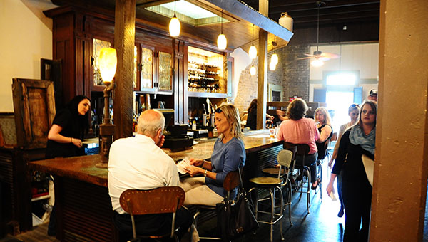 Guests enjoy drinks at the bar at the soft opening of the Coal Yard Bar and Grill in Old Town Helena on Wednesday, March 25. (Reporter Photo/Graham Brooks)