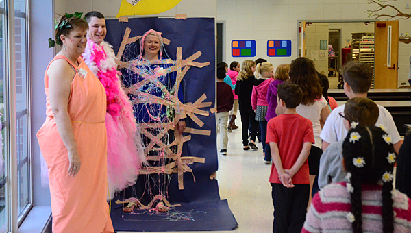 Students laugh as they pass, from left, Meadow View Elementary School Assistant Principal Carol Williamson, school resource officer Jamison Lee and Principal Rachea Simms on March 27. (Reporter Photo/Neal Wagner)