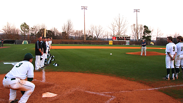 Retired Maj. Gen. James Darden, center, throws out the first pitch during a March 17 game between the Pelham Panthers and Helena Huskies. (Contributed)