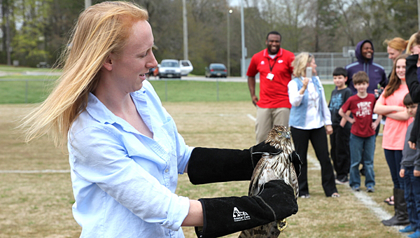 Auburn University veterinary student Emily Warman prepares to release a Cooper's hawk on March 23 as Warrior Center students look on. (Contributed/Keysha Thomaston)