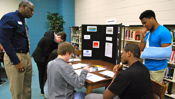 """Chelsea High School students work to incorporate insurance into real-world budgets during the Greater Shelby County Chamber of Commerce's """"Keeping it Real"""" program on March 12. (Reporter Photo / Molly Davidson)"""