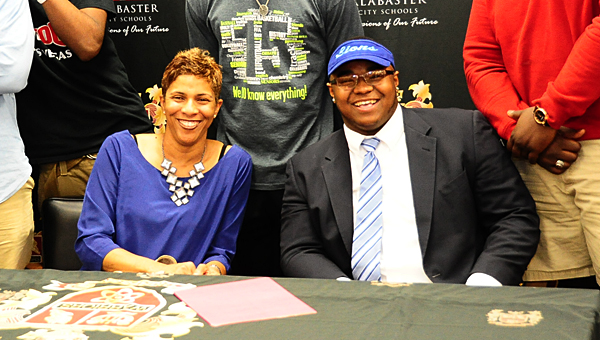 Marcus Lewis, right, joins his mother, Katrina, during a March 13 signing ceremony in the Thompson High School library. (Reporter Photo/Neal Wagner)