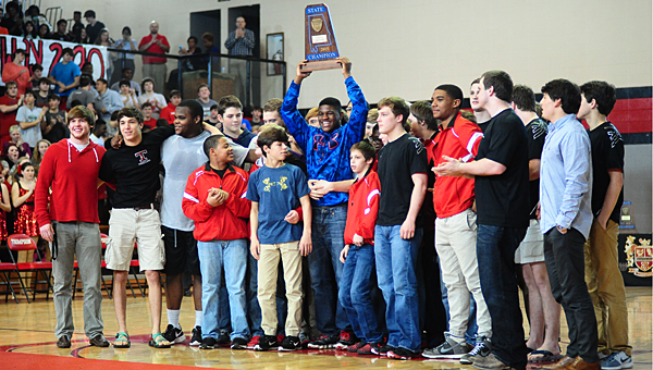 Thompson High School wrestler Nick Mobley, surrounded by his teammates, hoists the school's fifth-straight wrestling state championship trophy during a March 11 ceremony in the school's gym. (Reporter Photo/Neal Wagner)