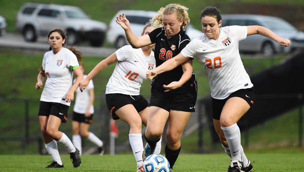 Thompson's Peyton Poe (20) tries to maintain possession against Sydney Dejohn and Hannah Amidon of Hoover during the Lady Warriors April 14 1-0 win. (Contributed / Troya Yoder)