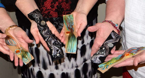 Students show off the cuff bracelets in progress during Ann Recotta's Beadapalooza class.