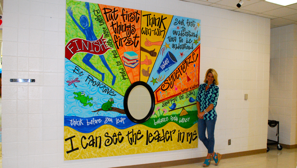 Local artist and Oak Mountain Elementary School parent, Vallie Pate stands with the mural she created for the school. (Reporter Photo / Molly Davidson)