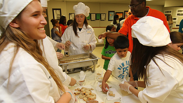 Students in Pelham High School's culinary arts institute present their creations to visitors at the Pelham City Schools Fine Arts Extravaganza on April 9. (Special to the Reporter/Eric Starling)
