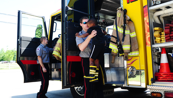 Alabaster firefighter Stephen Davis helps 4-year-old Kole Underwood out of the department's Engine No. 12 during a pre-k class visit to Fire Station No. 2 on April 30. (Reporter Photo/Neal Wagner)