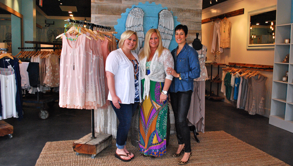 Saragrace Rockett, center, with friends Stacey Fox and Janet Wood stand in Rockett's new women's clothing boutique, Halo. (Reporter Photo / Molly Davidson)