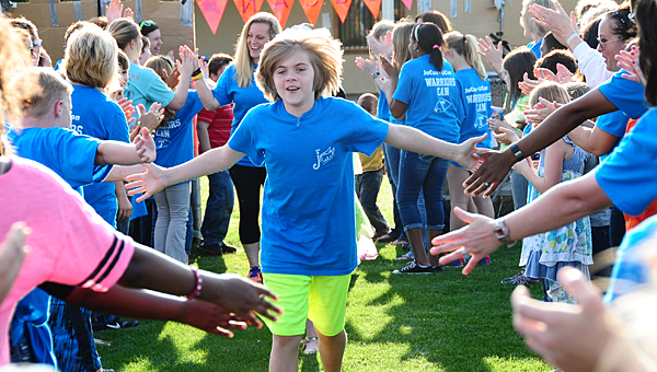 Jonathan David Cobb sprints through a crowd of Alabaster residents, teachers and students as they welcome his family to Buck Creek Park on April 20. (Reporter Photo/Neal Wagner)