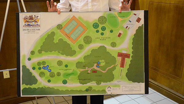 Sonya King of Two by Two Animal Rescue in Helena holds up a a proposal that would place a new dog park and animal shelter at Joe Tucker Park. (Reporter Photo/Graham Brooks)