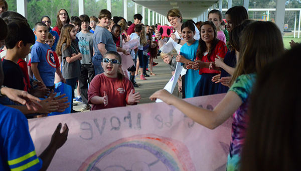 An HIS student competing in the Special Olympics is preparing to run through a poster before boarding the bus as other students and faculty cheer her on. (Reporter Photo/Graham Brooks)
