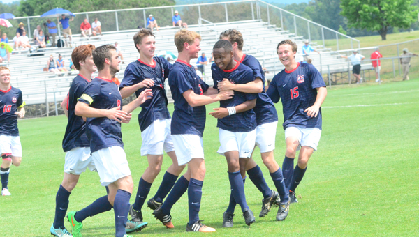 A group of Oak Mountain players swarm Kennedy Davis after his goal with less than 15 minutes to play in the 7A state championship put the Eagles on top of Auburn. Oak Mountain beat Auburn on May 9 by a final of 3-0 to win the first 7A state title. (Reporter Photo / Baker Ellis)