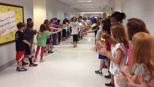 The third and fourth graders line the halls while the fifth graders walk the hall for one last time. (Contributed)