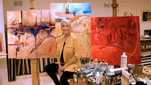 Lynne McCain in her studio with her most recent painting on the left.
