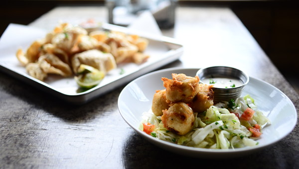 Appetizers include chicarrons and blue crab beignets, which are served with fennel-cabbage slaw.