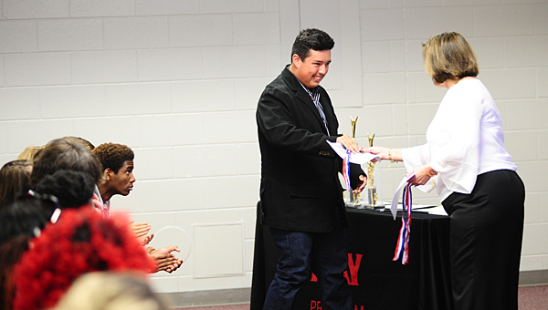 Leo Marquette, center, accepts an award from DAY Program Director Kathy Miller, right, as his classmates applaud him during a May 21 ceremony. (Reporter Photo/Neal Wagner)