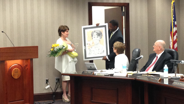 School Board member Derrick Murphy presents School Board President Donna Frazier with a portrait as thanks for her years of service to the School System during a May 11 meeting. (Reporter Photo / Molly Davidson)