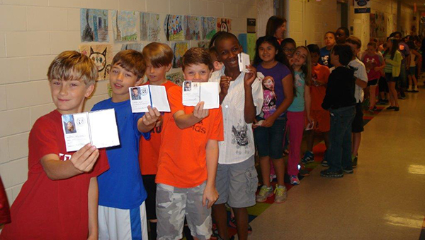 MES students hold up their passports that let's them enter different countries when the school hosted the first International Food Festival. (Contributed)