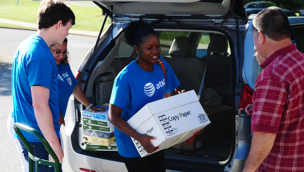 AT&T volunteer Sharanda Miller unloads a box of donated school supplies as she and several of her colleagues deliver the items to Meadow View Elementary School on May 13. (Reporter Photo/Neal Wagner)