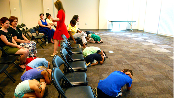 Kids demonstrate a safe position to take if sheltering from a tornado during meteorologist Meaghan Thomas's May 20 visit to the North Shelby Library. (Reporter Photo / Molly Davidson)