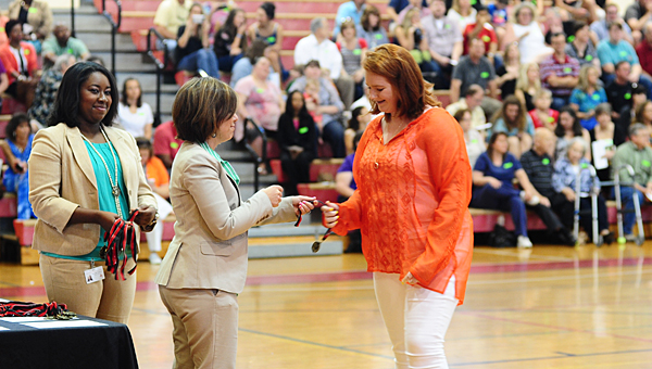 Thompson Middle School Principal Neely Woodley, second from left, presents an award to TMS eighth-grader Camille Horn, right, during the school's awards ceremony on May 20. (Reporter Photo/Neal Wagner)
