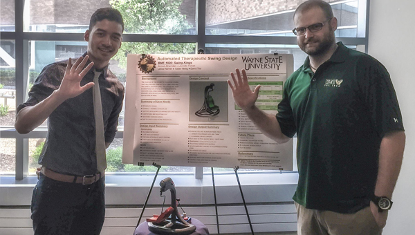 David Tes and Steven Patterson stand with the presentation board and small-scale model of their swing designed for individuals with special needs. (Contributed)