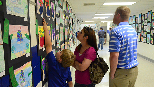 A HES student points out his artwork at the Family Night at the Art Show on Tuesday, May 5. (Reporter Photo/Graham Brooks)