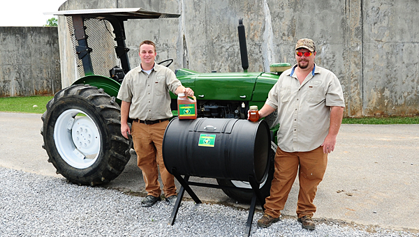 Alabaster Public Works employees Bill Atkinson, left, and Adam Roper, right, display biodiesel they made alongside a tractor running on 100 percent biodiesel. (Reporter Photo/Neal Wagner)