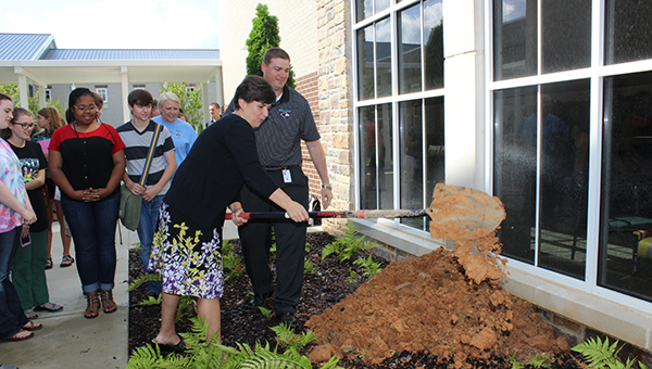 Helena High School Assistant Principal April Brand helps dig the hole where the time capsule was buried in the HHS courtyard on May 20. (Contributed)