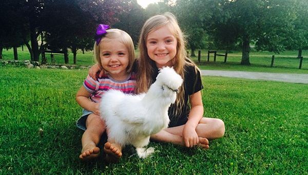 Sisters Lemley and Sawyer Griffin pose for a picture with their one-legged Silky Chicken Lieutenant Danielle who was rescused by their dad, Jamie, and now resides at their home. (Contributed)