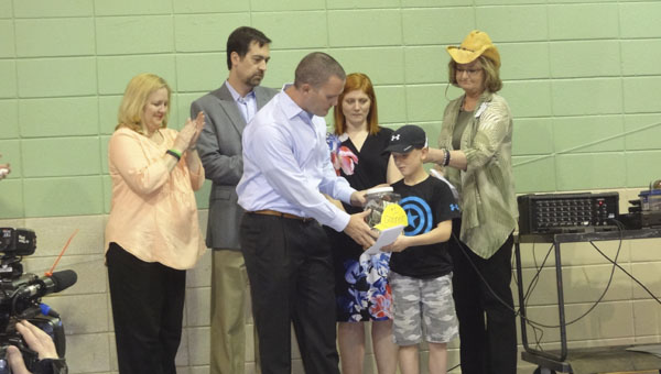 Connor Herrero presents donations he collected in memory of his friend, Connor Jacobs, to Dustin Chandler for Carly's Clubhouse during an assembly at Valley Elementary School on May 21. (Reporter Photo/Emily Sparacino)