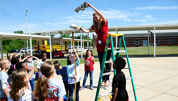 Meadow View Elementary School GRC teacher Lindsey Thigpen, right, prepares to test a group of students' design during the school's egg drop activity on May 14. (Reporter Photo/Neal Wagner)