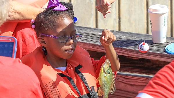 """A student admires the fish she caught during the annual """"Gone Fishin' not just Wishin' event at Oak Mountain State Park. (Special to the Reporter/Dawn Morrison)"""