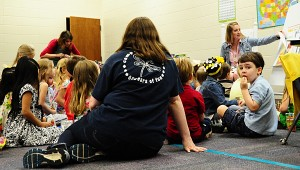 Incoming kindergartener Riley Marchman, right, enjoys his snack while listening to story time in the CVES cafeteria. (Reporter Photo/Neal Wagner)