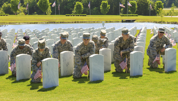 United States Air Force Airmen place flags at tombstones at the Alabama National Cemetery in Montevallo on May 23. (Special to the Reporter/Dawn Harrison)
