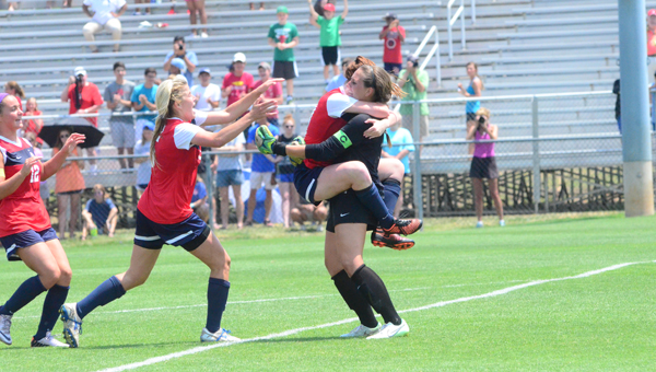 Katie Denny is mobbed by her teammates after blocking three of four penalty kicks in the 7A state finals on May 9 as the Lady Eagles from Oak Mountain wrapped up their second straight state championship. (Reporter Photo / Baker Ellis)