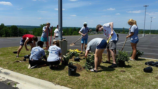 Members of the Helena Teen Council plant flowers and shrubbery at Helena High School for their last project of the year. (Contributed)