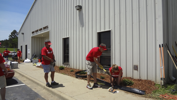 Volunteers from Keller Williams Realty replant a flowerbed in front of the Shelby Humane Society on May 14. (Reporter Photo/Emily Sparacino)