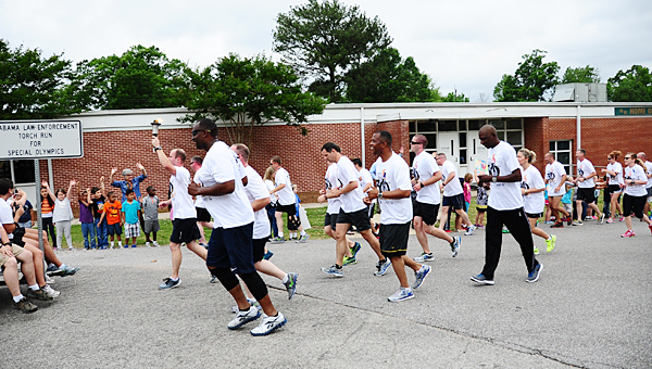 Law enforcement officers from across the state complete the Pelham leg of the 2015 Law Enforcement Torch Run as Valley Elementary School Students cheer them on. (Reporter Photo/Neal Wagner)