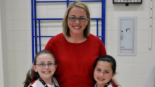 Kelly Hill, center, is a professor and the owner of Eagle Pride Cheerleading. Hill teaches the program at Inverness Elemenetary School to anywhere between 45-55 girls between kindergarten and the third grade. (Contributed)
