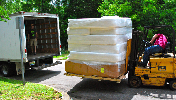 Fourteen mattresses are loaded into a truck bound for Big Oak Ranch in Springville. The mattresses are just a few of the 250 mattresses Bedzzz Express donated to local nonprofit organizations. (Reporter Photo / Molly Davidson)