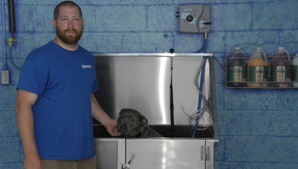 Steven Scott and Layla, the door greater at Alabama Pet Foods, try out the do-it-yourself dog wash at the a new storefront Camp Scotty. (Reporter Photo / Jessa Pease)