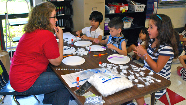 Students work with HIS teacher Julie Johnston to create polar bears out of paper plates, just one of the fun activities at IES ESL camp. (Reporter Photo / Molly Davidson)