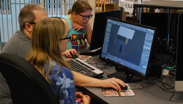 Courtney Cook works on animating a lightsaber duel between Luke Skywalker and Darth Vader on June 12 during a computer animation class at the North Shelby Library. (Reporter Photo / Molly Davidson)